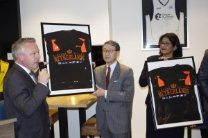 Paddy Roomer (links) overhandigt een shirt van Team Kingdom of the Netherlands aan Z. Exc. Jonghyun Choe en H. Exc. Eunice Eisden.
